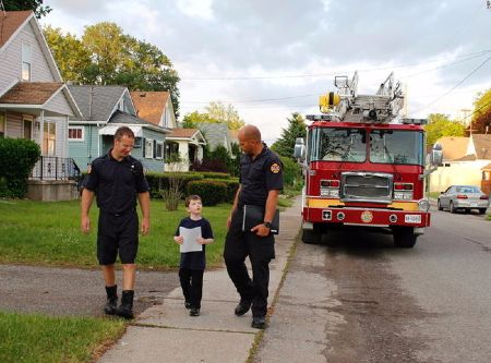 A boy and two firefighters walking on the street with a fire truck in the background. Property of Niagara Falls Review