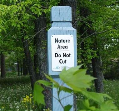 Sign on a pole stating: Nature Area, do not cut