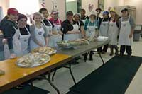 MYAC members serving dinner in a community kitchen
